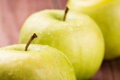 As maçãs verdes com hastes e gotas da água fecham-se acima Foto de Stock