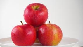 As maçãs vermelhas na placa e no gotejamento molham contra o fundo branco tiro da zorra de 4K ProRes filme