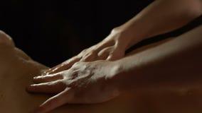 As massagens do massagista suportam da jovem mulher com azeite video estoque