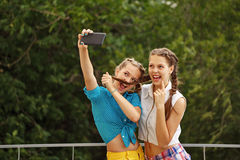 As melhores amigas que estão sendo fotografadas no parque Selfie do telefone da foto Fotografia de Stock