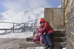as Menina-irmãs sentam-se em um abraço em etapas da casa de madeira nas montanhas imagem de stock