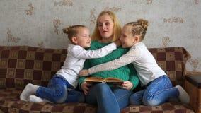 As meninas abraço e beijam sua mamã