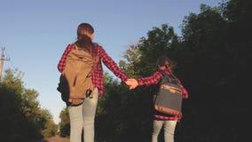 As meninas adolescentes viajam e guardam as m?os Menina do caminhante Viajantes das crian?as as meninas com trouxas est?o na estr video estoque