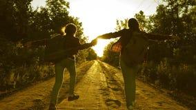 As meninas adolescentes viajam e guardam as m?os Viajantes das crian?as Menina do caminhante viajantes felizes das meninas com as filme