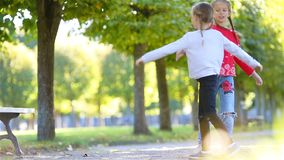 As meninas adoráveis pequenas que têm o divertimento no outdoorsÑŽ ensolarado morno do dia do outono caçoam na queda vídeos de arquivo