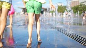 As meninas adoráveis pequenas têm o divertimento na fonte da rua no dia ensolarado quente filme
