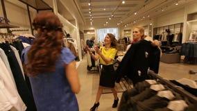 As meninas alegres escolhem sapatas e roupa na loja vídeos de arquivo