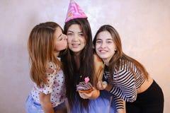 As meninas amigáveis bonitas comemoram o aniversário de seus amigos fêmeas imagens de stock royalty free
