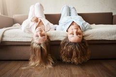 As meninas apenas querem ter o divertimento Amigas bonitas que encontram-se no sofá de cabeça para baixo com o assoalho tocante d Fotografia de Stock Royalty Free