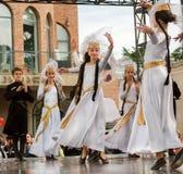 As meninas artísticas felizes que dançam no branco Georgian tradicional vestem-se durante o desempenho do dia da cidade Fotografia de Stock Royalty Free