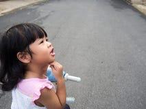As meninas asiáticas montam uma bicicleta e o pensamento, sua cara olha o suspeito e tem perguntas foto de stock