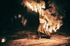 As meninas ativas realizam truques para a mostra do fogo na noite Imagens de Stock