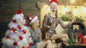 As meninas bonitas bebem o champanhe e queimam luzes de Bengal perto da árvore de Natal Meninas engraçadas no partido do ano novo filme