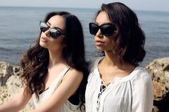 As meninas bonitas com cabelo escuro vestem a roupa e óculos de sol elegantes ocasionais Foto de Stock