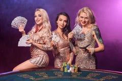 As meninas bonitas com os penteados perfeitos e composição brilhante estão levantando a posição em uma tabela de jogo Casino, p?q fotos de stock royalty free
