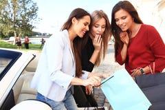 As meninas bonitas com sacos de compras estão discutindo compras e estão sorrindo ao inclinar-se em seu carro Foto de Stock