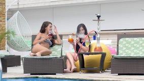 As meninas bonitas das bisbolhetices nos roupas de banho fumam o cachimbo de água e bebem cocktail perto da associação no resto d vídeos de arquivo