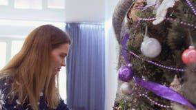 As meninas bonitas decoram a árvore de Natal e dão alto-cinco vídeos de arquivo