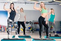 As meninas bonitas dos esportes em uma classe de ginástica aeróbica levantam Imagens de Stock