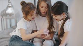 As meninas bonitas estão sentando-se no sofá e estão mostrando-se lhe algo interessante e engraçado no smartphone video estoque