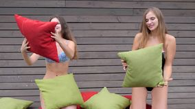 As meninas bonitas nos roupas de banho jogados com descansos coloridos, amigas bonitas têm o bom tempo video estoque