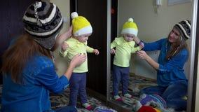 As meninas brincalhão da família que medem chapéus mornos do inverno aproximam o espelho video estoque