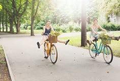 As meninas chiques do boho feliz montam junto em bicicletas no parque Imagens de Stock