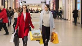 As meninas com sacos de papel andam ao longo do corredor no shopping video estoque