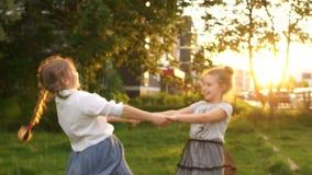 As meninas da estudante gerenciem em conjunto no parque de nivelamento, férias de verão, infância feliz Uma menina cai na grama video estoque