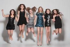 As meninas da forma que saltam junto e que olham a câmera sobre o fundo cinzento do estúdio imagem de stock