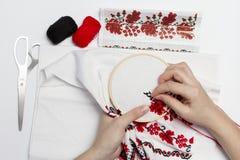 As meninas das mãos bordam o teste padrão usando o quadro Imagens de Stock Royalty Free
