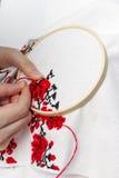 As meninas das mãos bordam o teste padrão usando o quadro Fotografia de Stock