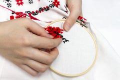 As meninas das mãos bordam o teste padrão usando o quadro Foto de Stock