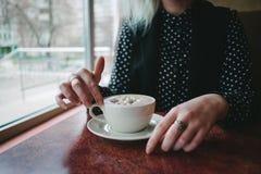 As meninas das mãos tomam uma xícara de café com marshmallows em um café acolhedor Bebida quente para o café da manhã Imagens de Stock Royalty Free