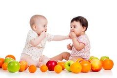 As meninas de bebês que comem o alimento saudável frutificam no branco Fotografia de Stock Royalty Free