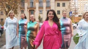 As meninas de encantamento em vestidos bonitos contaminam na rua A semana de moda positiva do tamanho Movimento lento video estoque