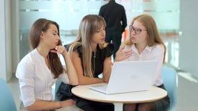 As meninas discutem o trabalho, olhar no portátil no centro de negócios Caminhada após o pessoal filme