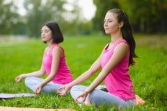 As meninas do esporte da aptidão no sportswear que faz a aptidão da ioga exercitam exterior Imagem de Stock Royalty Free