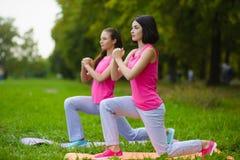 As meninas do esporte da aptidão no sportswear que faz a aptidão da ioga exercitam exterior Fotos de Stock Royalty Free
