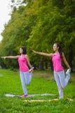 As meninas do esporte da aptidão no sportswear que faz a aptidão da ioga exercitam exterior Imagens de Stock