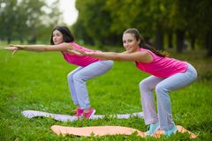 As meninas do esporte da aptidão no sportswear que faz a aptidão da ioga exercitam exterior Fotografia de Stock Royalty Free
