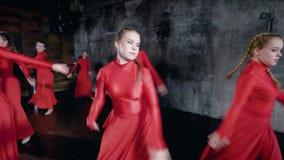 As meninas do estudante estão dançando a composição contemporânea em um salão de formação escuro na escola das artes, saltando filme