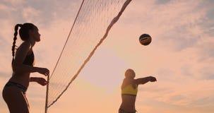 As meninas do fósforo do voleibol de praia bateram a bola no movimento lento no por do sol na areia vídeos de arquivo