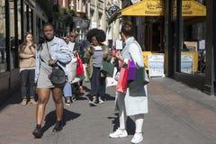 As meninas do moderno vestiram-se no estilo fresco do londrino que andam na pista do tijolo, uma rua popular entre povos na moda  Foto de Stock