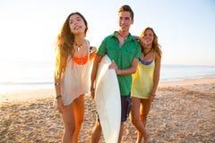 As meninas do surfista com o menino adolescente que anda na praia suportam Imagem de Stock