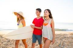 As meninas do surfista com o menino adolescente que anda na praia suportam Fotografia de Stock