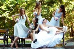 As meninas e a noiva bonitas falam o assento no banco Imagem de Stock Royalty Free