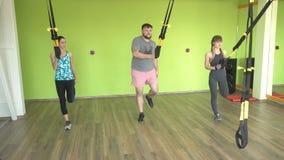As meninas e os homens das classes do grupo com um instrutor são contratados nos laços de TRX, na perda de peso e no desenvolvime vídeos de arquivo