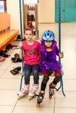 As meninas em patins de rolo sentam-se no balanço de suspensão dentro imagem de stock royalty free