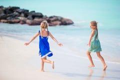 As meninas engraçadas felizes pequenas têm muito divertimento na praia tropical que joga junto Fotos de Stock Royalty Free